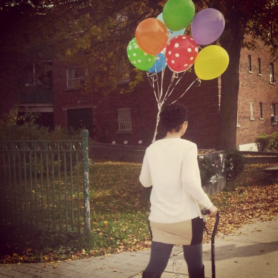 Cane in one hand, balloons in the other.